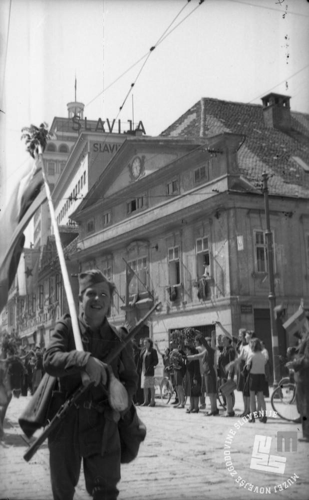 Prihod partizanov pred Figovcem, v ozadju nebotičnik. Foto Rudi Stopar, hrani MNZS.